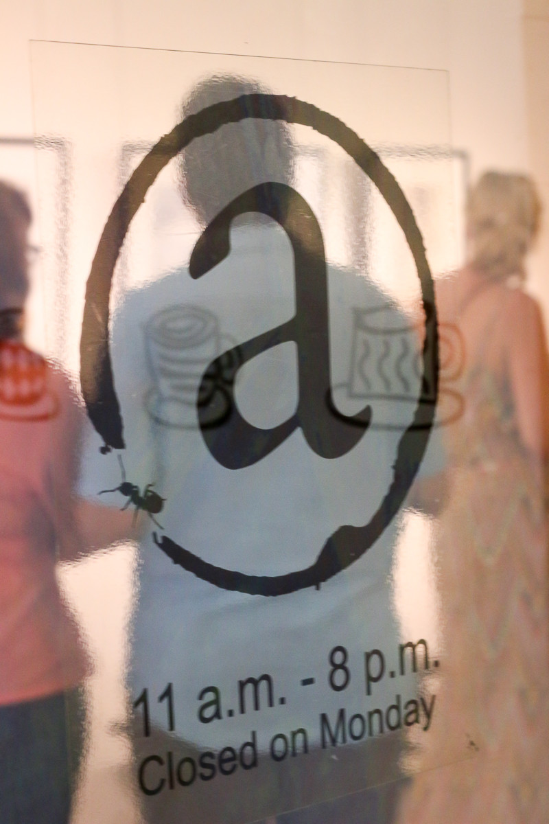 view into an art exhibition through a glass door
