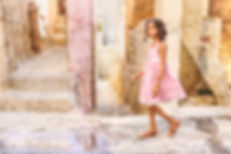 Girl in a pink dress walks on a narrow alley way.