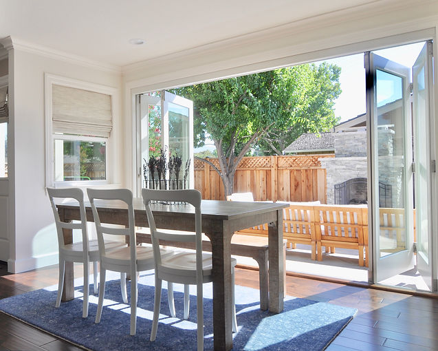 Dining room table looking out to the backyard that has a fireplace. Jennifer Kretschmer Architect.