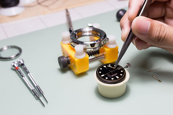The watchmaker is repairing the mechanic