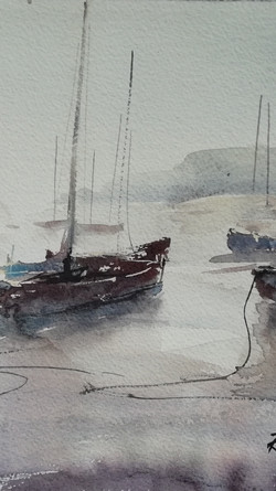 Bright afternoon on the beach, boats sat waiting for the tide