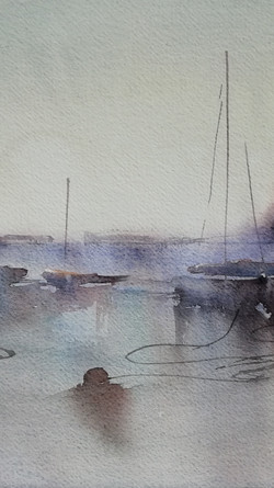 A misty morning in the harbour, boats resting on the sand