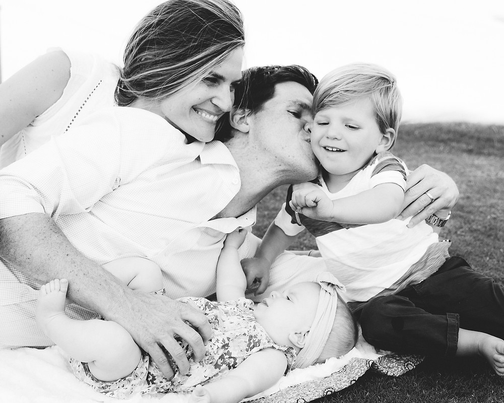 family cuddles and kisses black and white