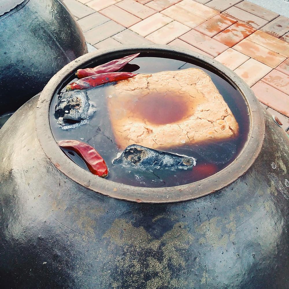 meju and salt water in earthenware jar