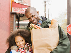 Father holding groceries and walking with daughter