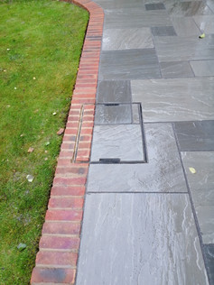 Kandla Grey Natural Stone Paving with Brick Edging and Recessed Inspection Cover