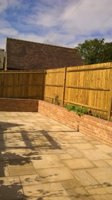 Concrete Paving with Brick Retaining Wall and Boundary Close-board Fencing
