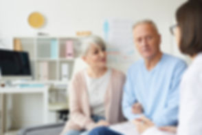 senior-couple-listening-to-doctor-in-cli