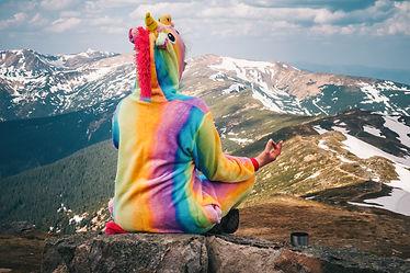 Female hiker in a unicorn suit meditatin