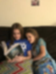 picture of CES student reading The One and Only Ivan to her sister