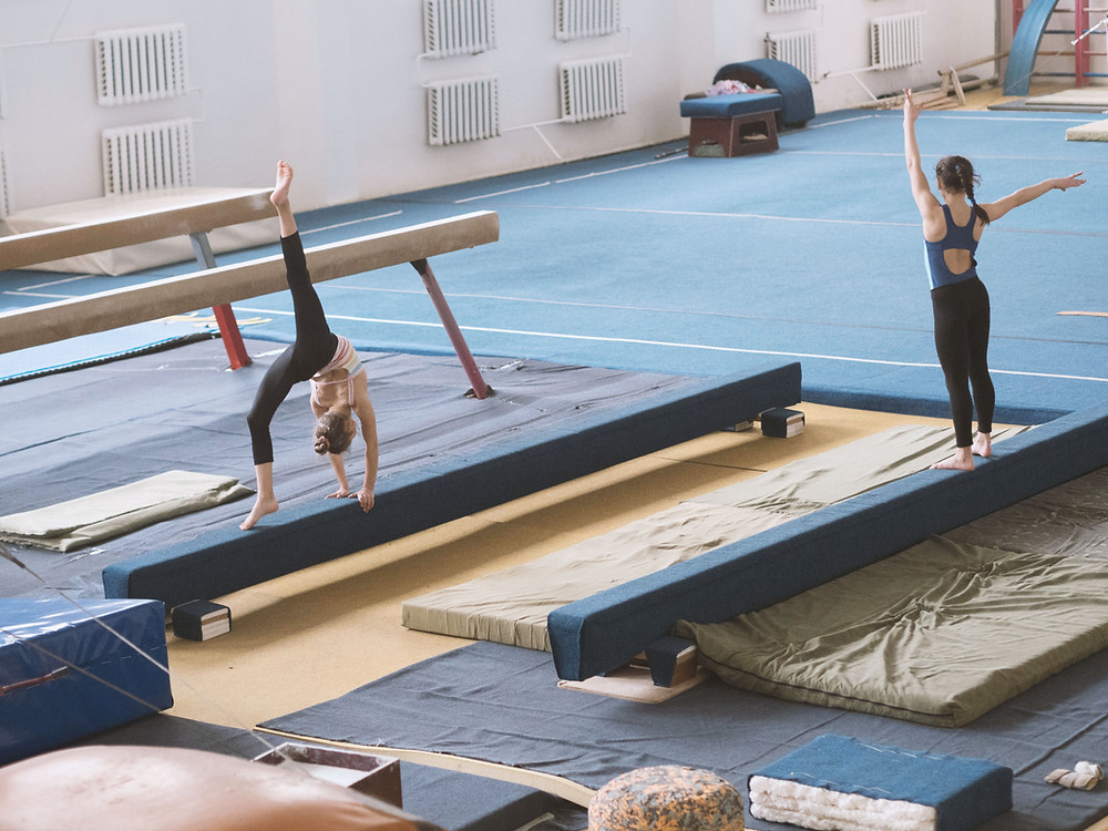 2 girls practicing gymnastics on beams