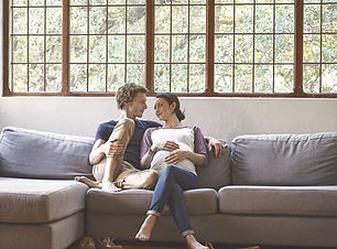 loving-expectant-couple-sitting-on-sofa-