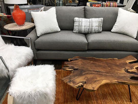 Gray sofa with gray and white pillows with a white fuzzy chair/ottoman and live edge table
