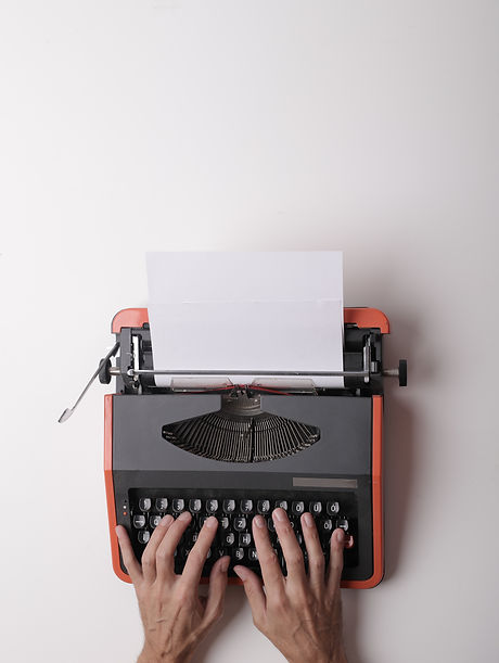 red typewriter male hands pexels-andrea-
