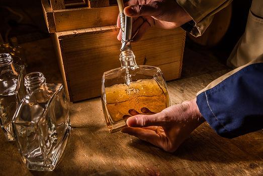 Werbefotografie Timo Lutz. Whiskeyabfüllung. Flasche und Händ. Fotografenmeister werden in Kiel. Photo+Medienforum Kiel