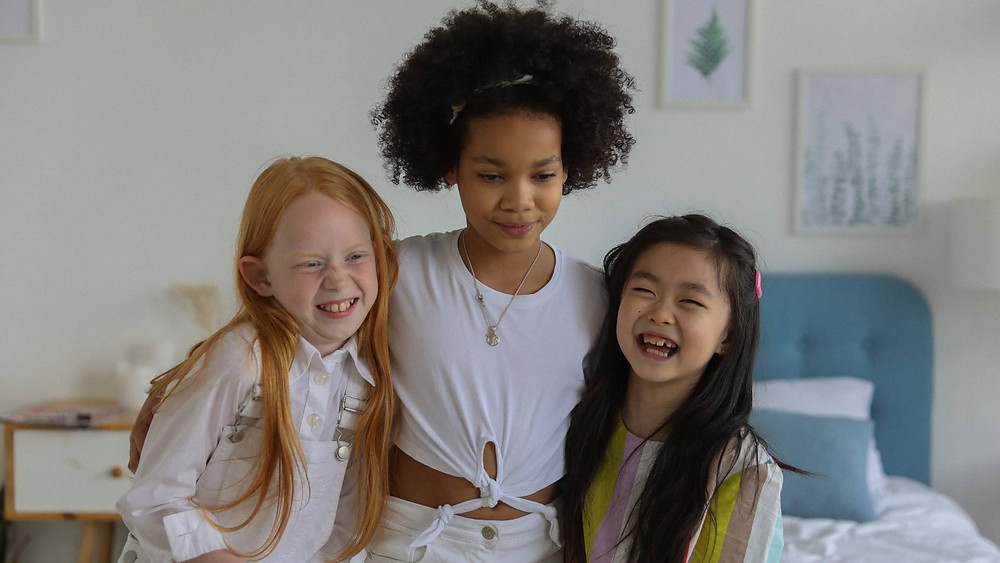 Three girls, from left: one with long straight auburn hair, one with mid-length curly brown hair, one with long straight brown hair.