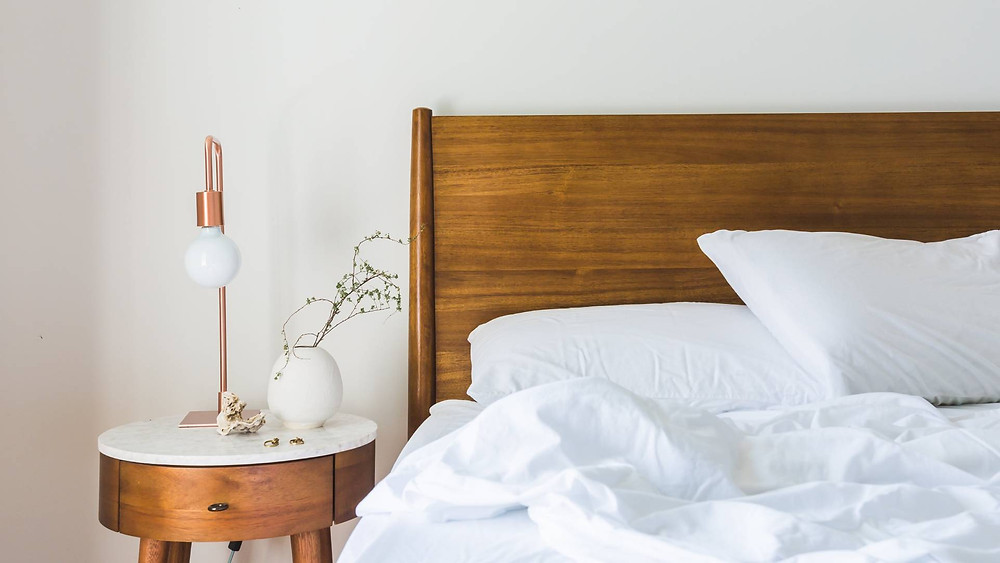 Brown wooden bed with white bedspread