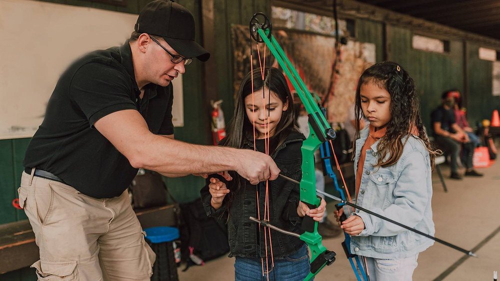 Man showing two young girls how to hold a plastic bow and arrow
