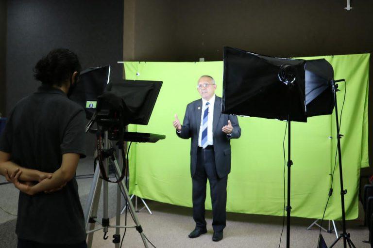 Imagem com um senhor de paletó em um estúdio falando para a câmera. Através dele, há um pano verde de fundo. Na frente dele, o cinegrafista acompanha a fala dele atrás da câmera.