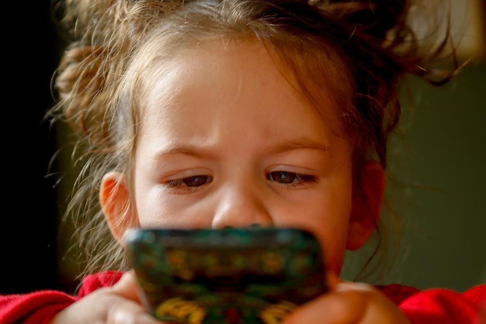 Garotinha loira segura um celular bem próximo ao rosto