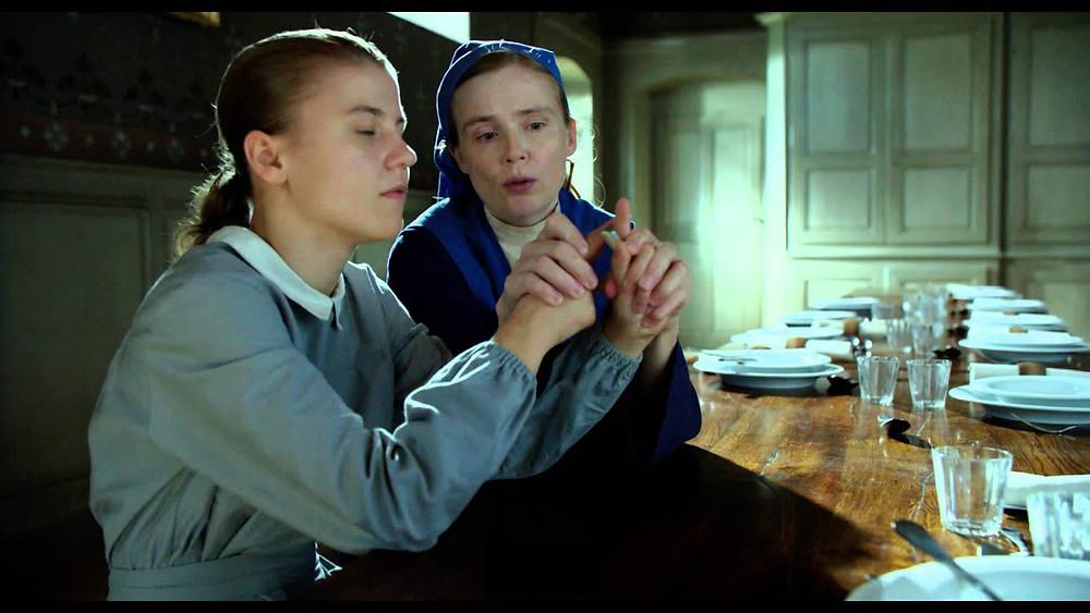 """Cena do filme """"A Linguagem do Coração"""" em que uma freira ensina uma surdacega de nascença a se comunicar através da libra tátil. A menina surdacega está aprendendo a fazer o sinal de """"faca"""", utilizando os dois indicadores, passando um pelo outro simulando o movimento de corte."""