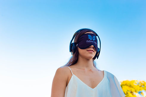 Mulher branca de cabelo longo, castanho escuro e liso, usando um headphone e protetor de olhos participa de um experimento sensorial.