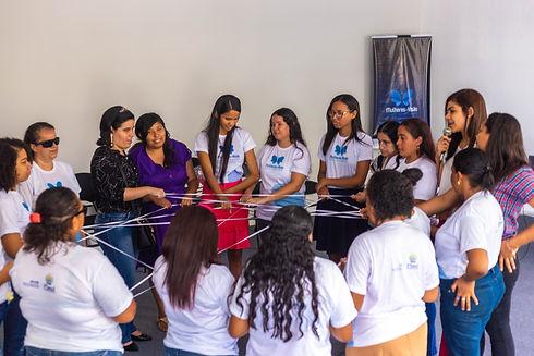 Mulheres em círculo construindo uma teia com elástico.