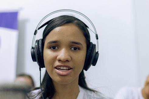 Jovem parda de cabelos pretos, longos e lisos, usando um headphone.