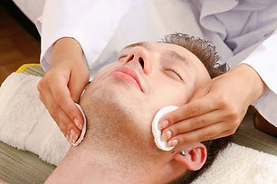 Female hands cleaning man's face with co