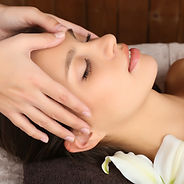 Beautiful young woman in spa salon with spa stones taking head massage.jpg