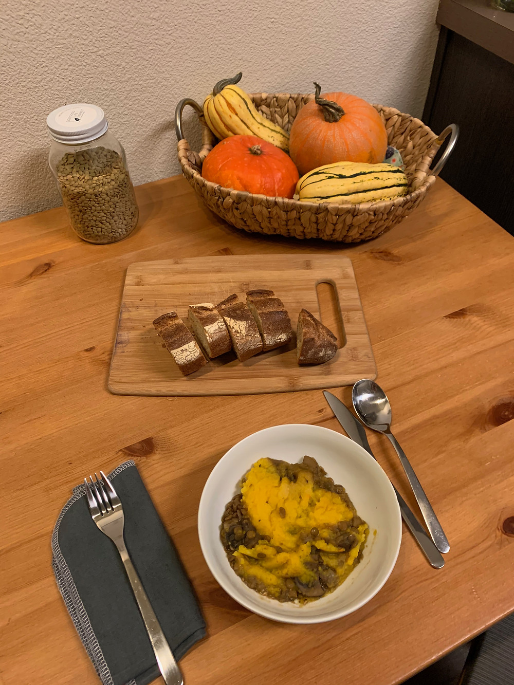 A bowl of shepherd's pie, sliced bread, a glass jar of lentils, and basket of squash sit on a wooden dining table.