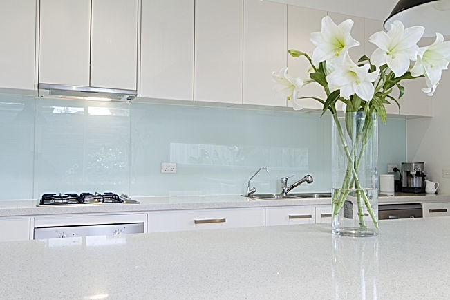 Flowers on white kitchen bench with spla