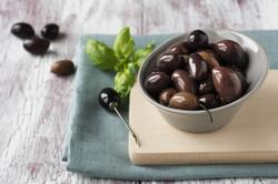 Pickled black olives in a bowl on wooden background.
