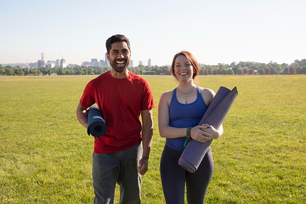 Man and woman smiling as they hold yoga mat in a park on a sunny day