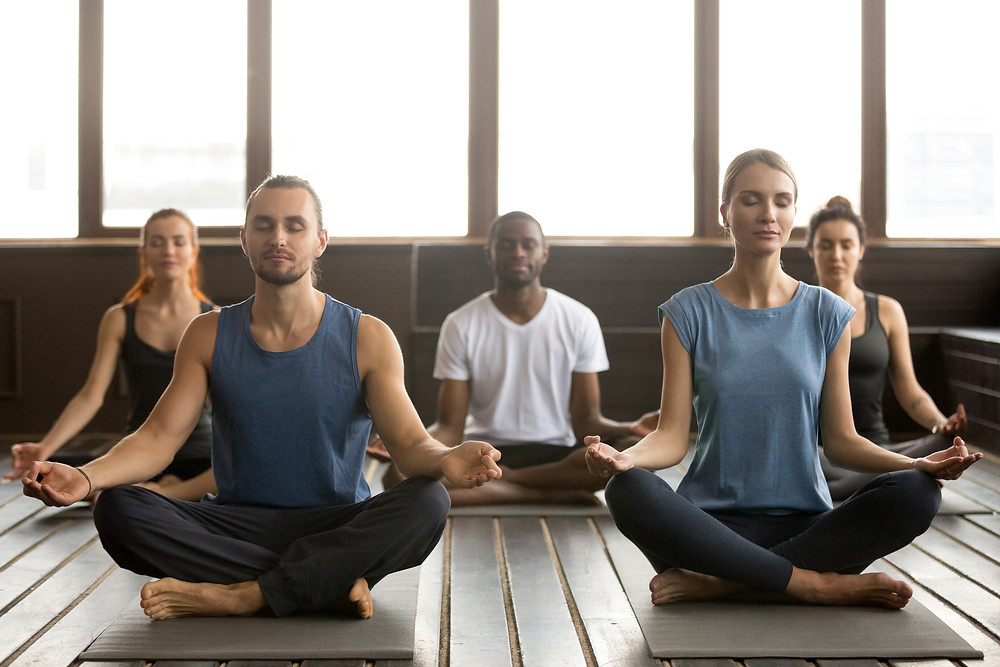 Young diverse group of people doing yoga breathing exercises