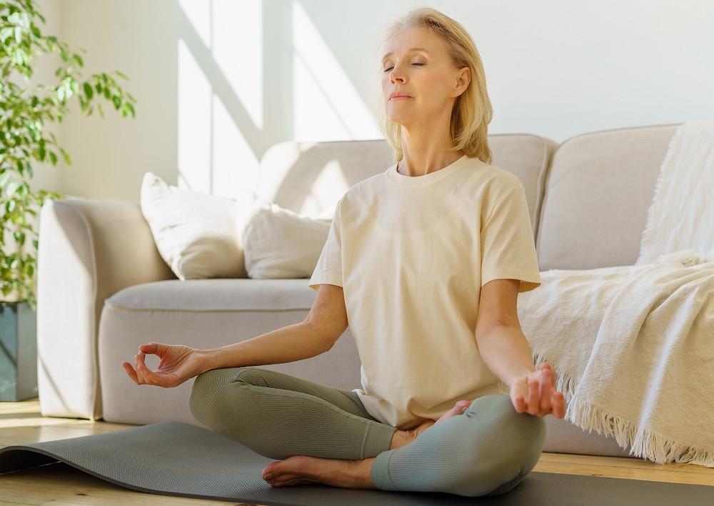mature-woman-doing-ujjayi-pranayama-in-cross-legged-pose-on-yoga-mat