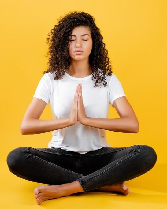 Woman in easy pose (Sukhasana) doing pranayama