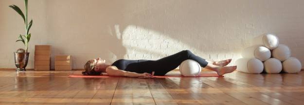 Woman in Corpse Pose doing yoga breathing exercises
