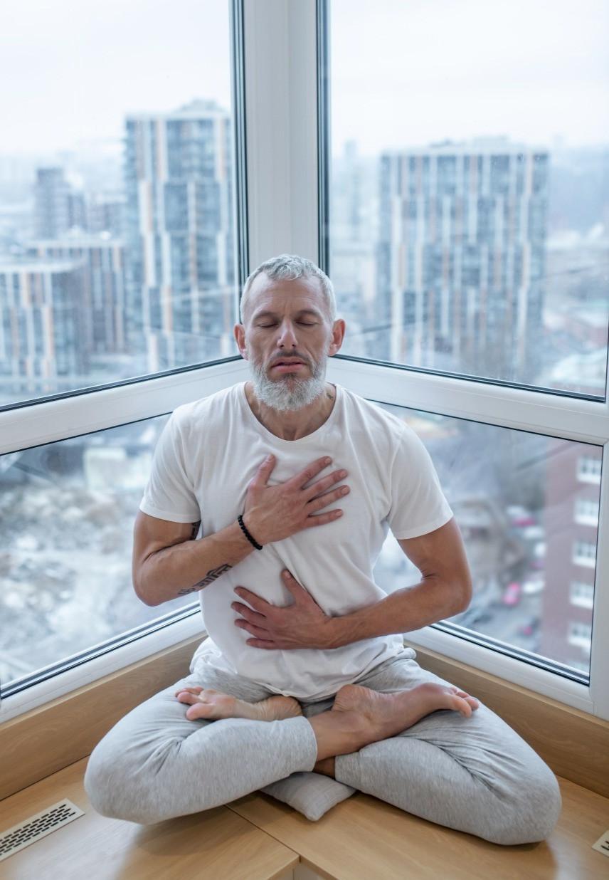 Man practices three-part breath in Lotus Posture