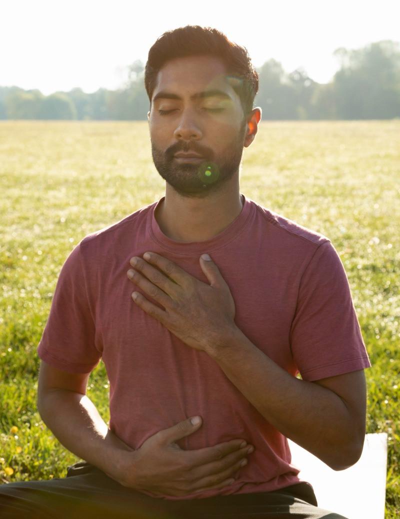 Man doing Bhastrika Pranayama or Bellows Breathing in Yoga pose
