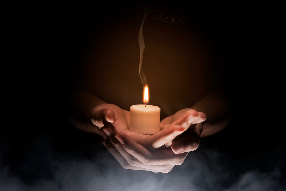 Man holding candle in palm in dark room