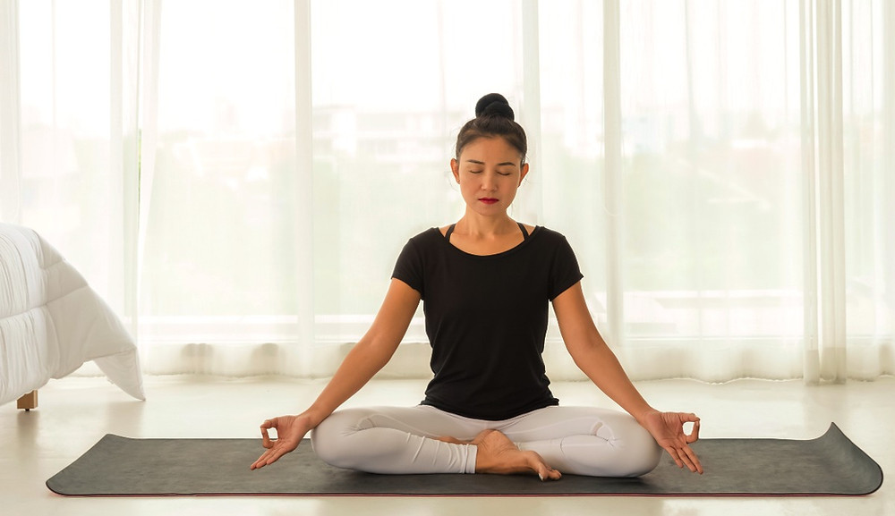 Asian woman doing Mula Bandha (Root Lock) in cross-legged yoga pose