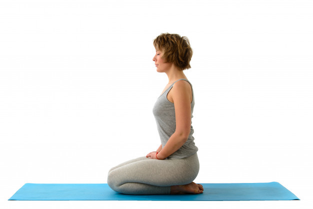 Woman doing yoga breathing exercises in Hero pose with Brahma Mudra