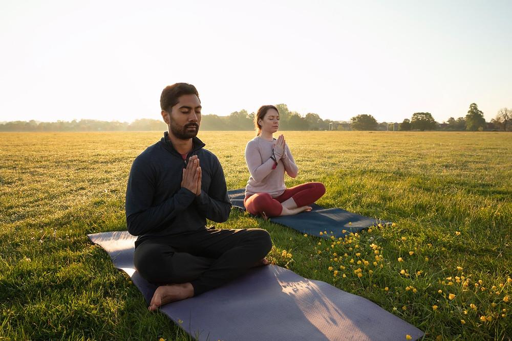 Man and woman doing Bhastrika Pranayama at sunrise in a park