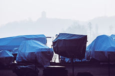 Several boats wrapped in tarpaulins.jpg