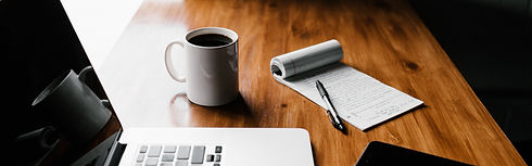 Desk with laptop, coffee mug, notepad, pen and smartphone.