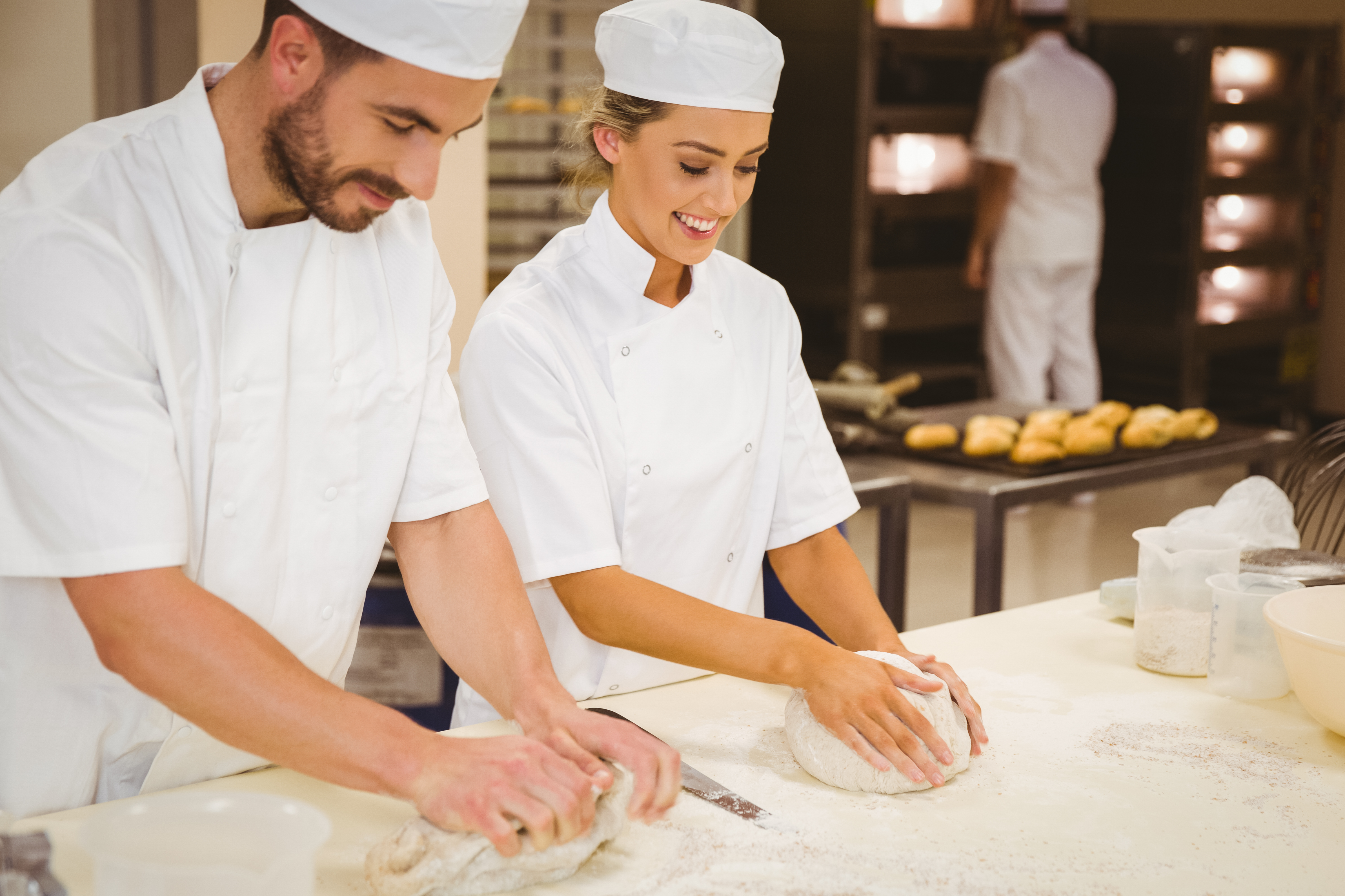 Team of bakers kneading dough in a comme