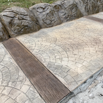 roman fan with wood plank bands stamped concrete parking pad with solid concrete retaining wall