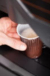 Coffee maker pouring hot espresso coffee