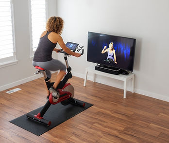 woman-exercising-on-spin-bike-in-home-picture-id932459344.jpg
